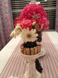 Cut wine bottle vase, in the middle of standing corks on a candle holder. Daisies and Roses.